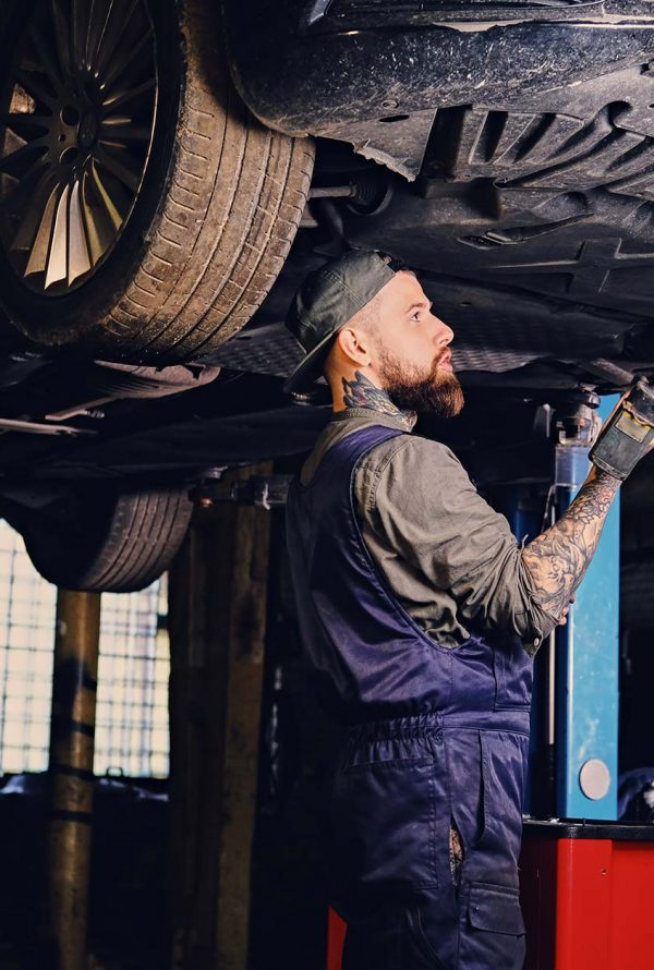bearded-mechanic-working-with-the-cars-chassis-in-small.jpg